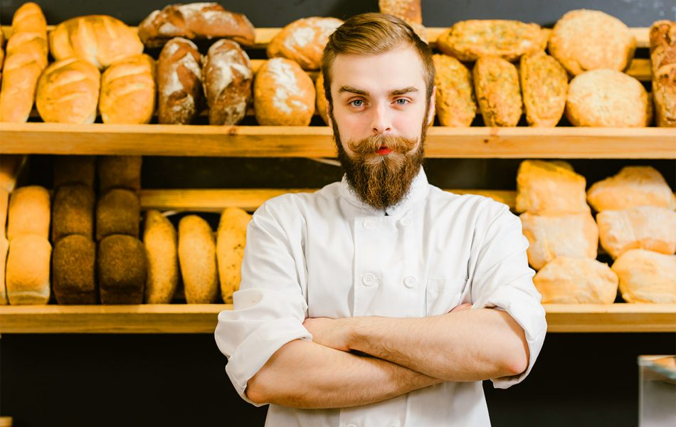 Baker stands proudly in front of fresh baked bread for restaurant video marketing