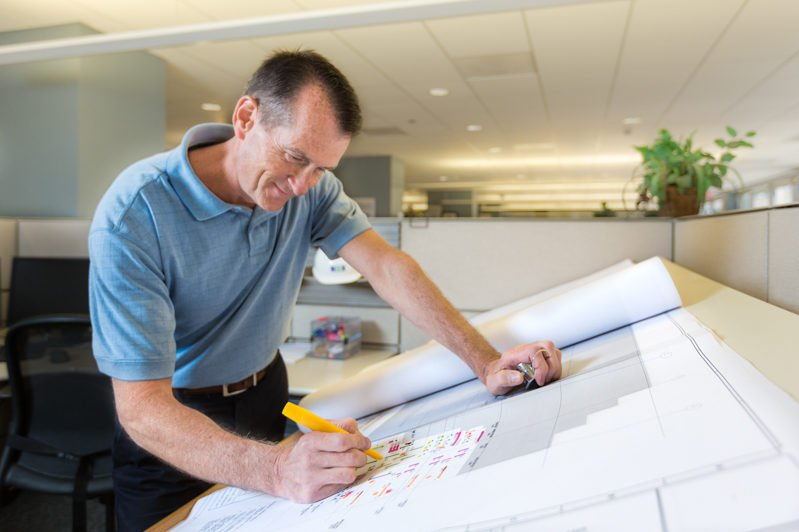 Man stands at drafting table, reviewing large blueprints with highlighter as photographed by digital marketing company, Loudbyte