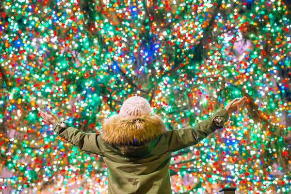 The back of a young girl, arms open wide as she admires a brightly lit Christmas tree for a web and tv commercial created by Loudbyte