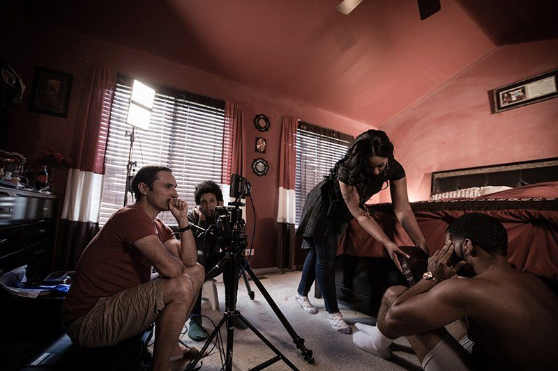 Director, DP and actors are seated in a bedroom prepping to shoot a scene from a music video