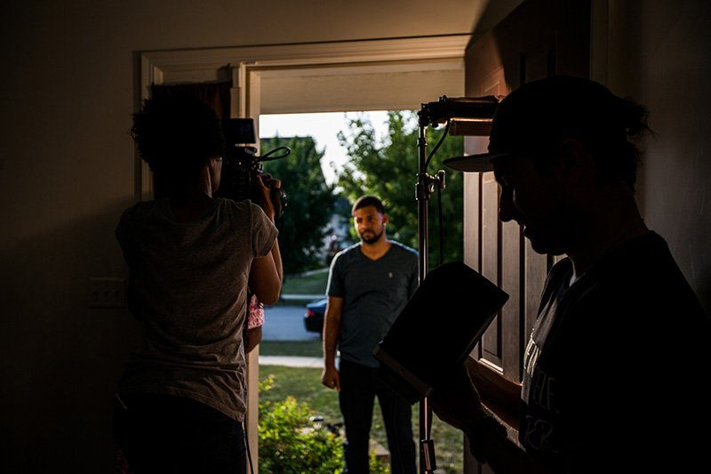 Director, DP and Actor in position at the front of a house, waiting for action