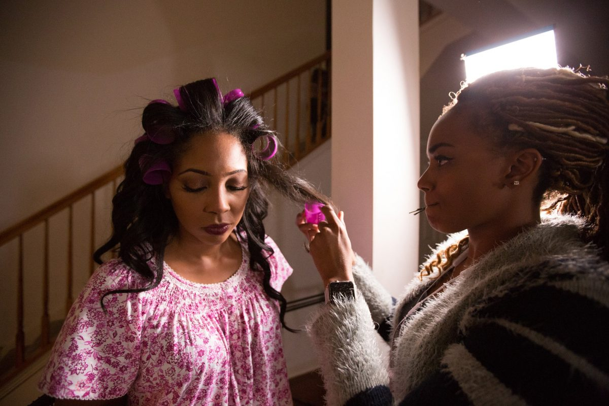 A singer gets her hair curled by a makeup artist as part of a Christian Music Video produced by Loudbyte