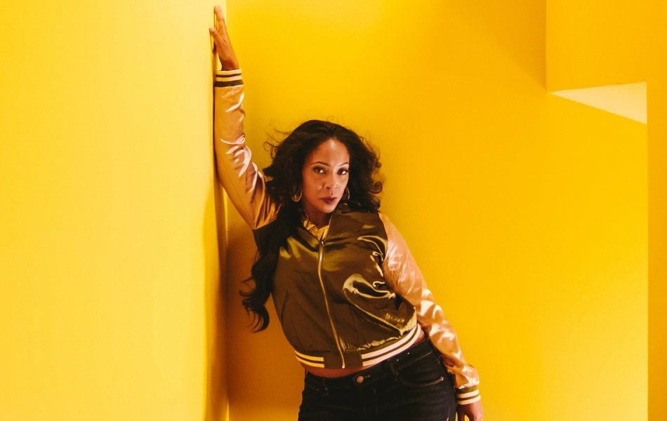 singer leans against a bright yellow wall for a promotion photo for a music video produced by Loudbyte